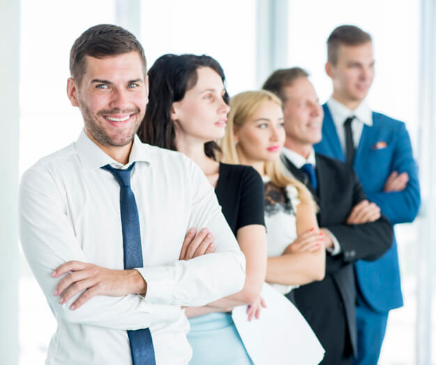 portrait of a happy manager with his employees standing in a row 23 2147900116 1